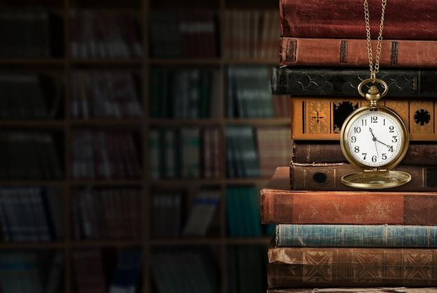 Vintage klok aan een ketting met oude vintage boeken