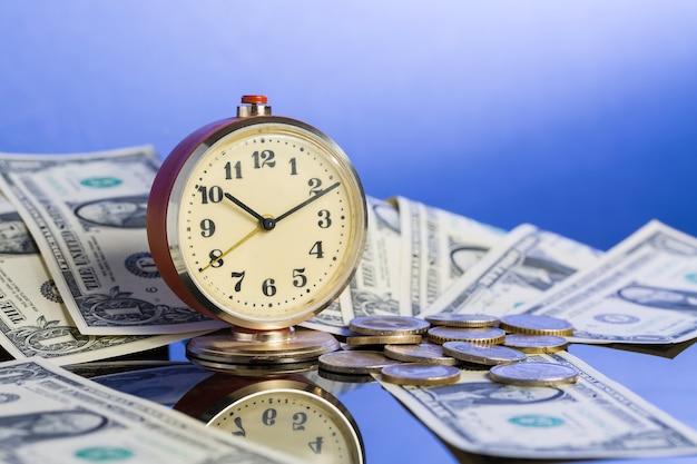 Vintage klok in de buurt van amerikaanse dollarbiljetten en munten