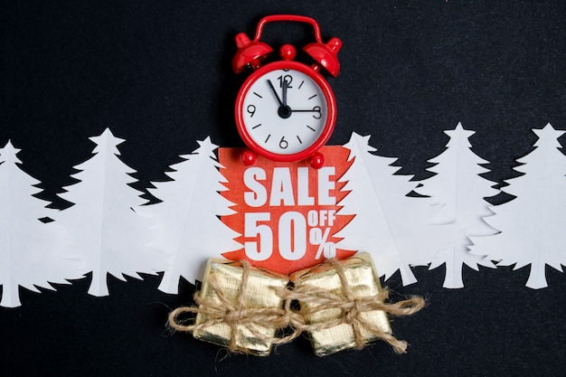 Vintage klok met geschenkdozen op een rode kortingssticker met een ambachtelijke envelop en papieren kerstbomen
