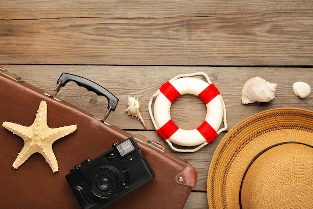 Vintage koffer en strand accessoires op grijze achtergrond