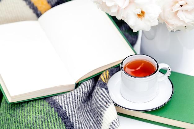 Vintage kopje thee in de buurt van open boek bloemen witte wilde roos in vaas warme plaid op witte tafel buiten
