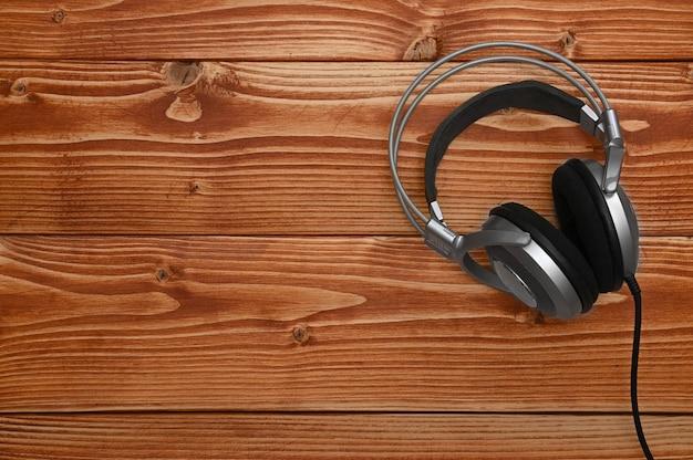 Vintage koptelefoon voor het luisteren naar geluid en muziek op een bruine houten