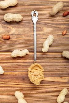 Vintage lepel met romige pindakaas op een bruin houten tafel. in de buurt van de pindakaas liggen pinda's in de schaal en gepelde pinda's. plat leggen van pindapasta voor het koken van ontbijt. veganistisch voedselconcept