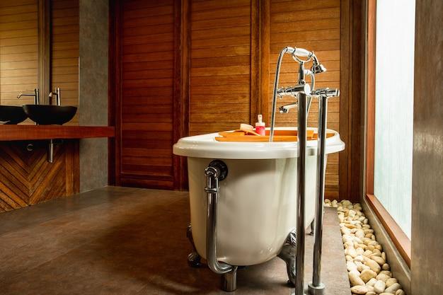 Vintage ligbad en groot raam met wastafels in houten badkamer.
