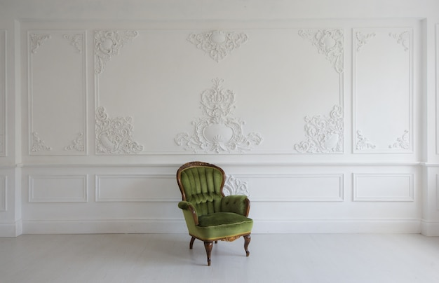 Vintage luxe groene fauteuil in witte kamer over muurontwerp bas-reliëf stucwerk lijstwerk roccoco-elementen