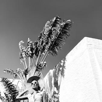 Vintage meisje in modeaccessoires hoed en zonnebril op palmlocatie strand retro sfeer