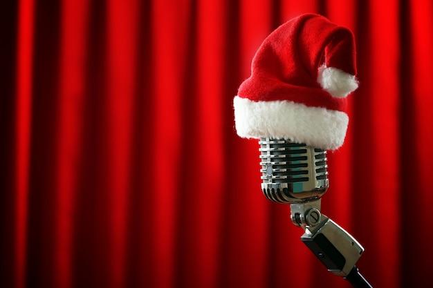 Vintage microfoon met kerstmuts op rode gordijnachtergrond