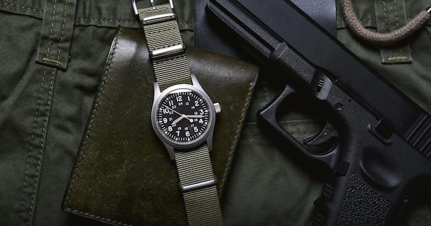 Vintage militaire horloge portemonnee en pistool op legergroene achtergrond, klassiek uurwerk mechanisch polshorloge, militaire mannen mode en accessoires.