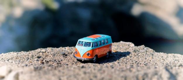 Vintage miniatuur oranje en blauw busje. reizen concept