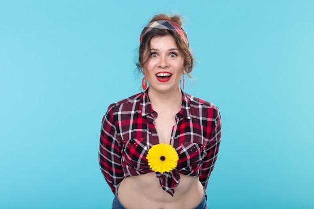 Vintage, mode en floristisch concept - vrouw met gele bloem in retro stijl op blauwe muur
