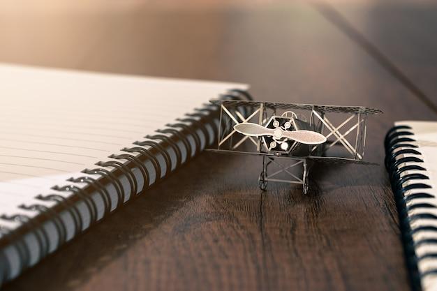 Vintage modelvliegtuig op houten tafel met notebook en notepad vrijheid van gedachte concept achtergrond.