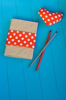 Vintage notitieboek, hart met rode stippen stof en houten potloden