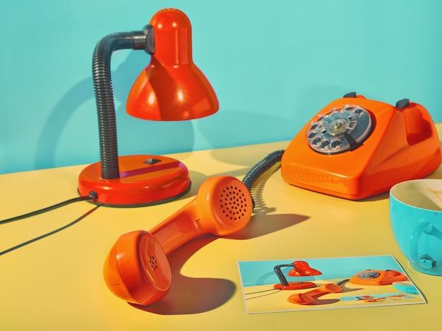 Vintage oranje telefoon, tafellamp en fotoprint in vintage posterstijl