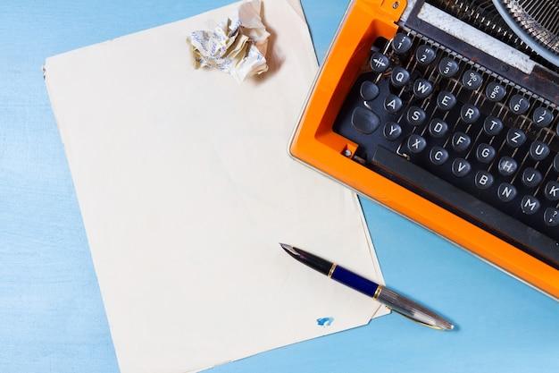 Vintage oranje typemachine en vellen papier