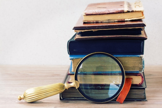 Vintage oude boeken gestapeld op tafel met antiek zoekglas