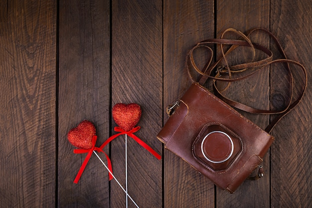 Vintage oude camera met harten op rustieke houten tafel. bovenaanzicht
