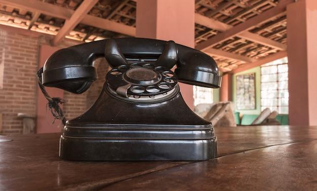 Vintage - oude zwarte telefoon retro op een houten tafel