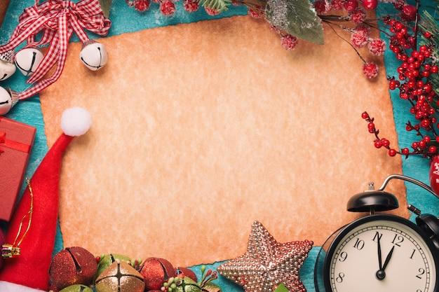 Vintage papier, kerstmuts, klok en decoraties op blauwe houten tafel.