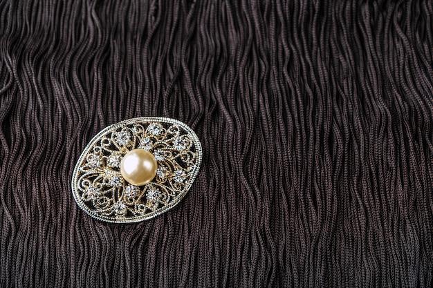 Vintage parel sieraden broche op zwarte jurkje.