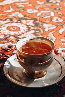 Vintage porseleinen theetijd op turks tapijt, zwarte thee met rook in een porseleinen kop en schotel op het zonlicht, aziatische theeceremonie, hete stoom