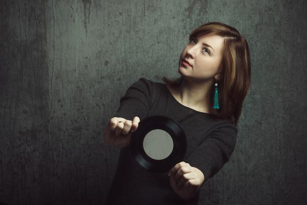 Vintage portret van mooi stijlvol meisje met turquoise oorbellen en vinyl record in handen op grijs