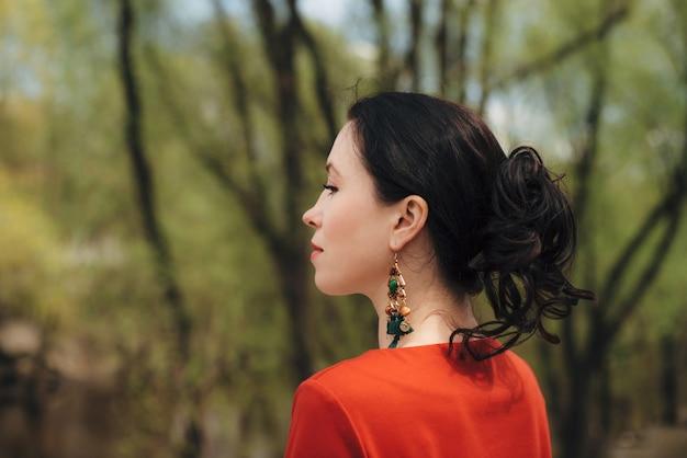 Vintage portret van prachtig meisje met zwart krullend haar met grote groene oorbellen en rode jurk