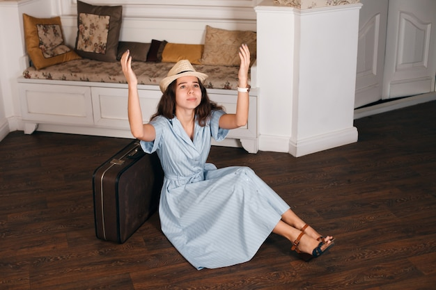 Vintage reisconcept met een jonge vrouw in hoed zittend op de vloer in de buurt van haar koffer in de woonkamer
