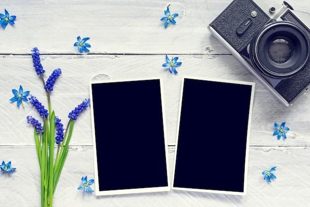Vintage retro camera, blanco fotolijsten en lenteblauwe bloemen