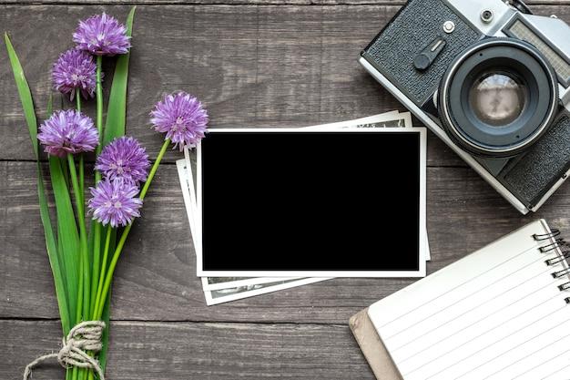 Vintage retro camera met lege fotolijstjes, paarse wilde bloemen en gevoerd notitieblok op rustieke houten tafel