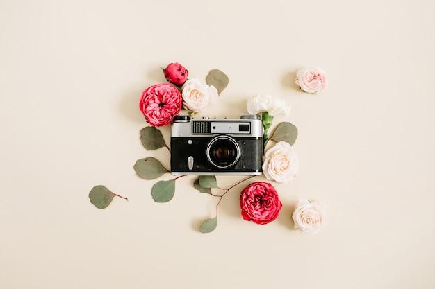 Vintage retro camera, rood en beige roze bloemknoppen patroon op bleek pastel beige