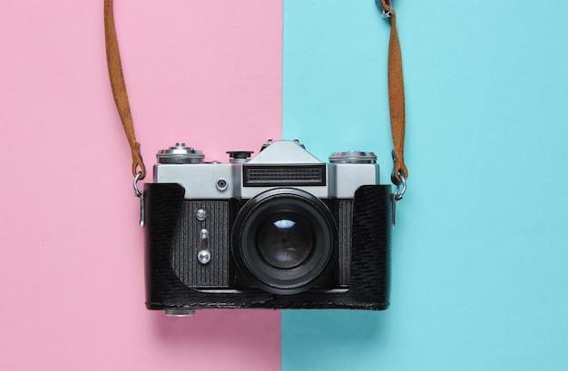 Vintage retro filmcamera in lederen omslag met riempje op roze blauw.