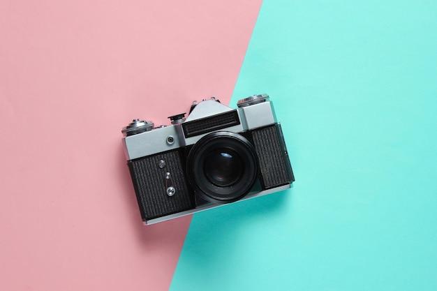 Vintage retro-stijl filmcamera op roze blauw.