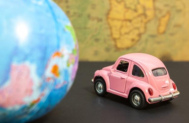 Vintage roze auto en globe op kaart