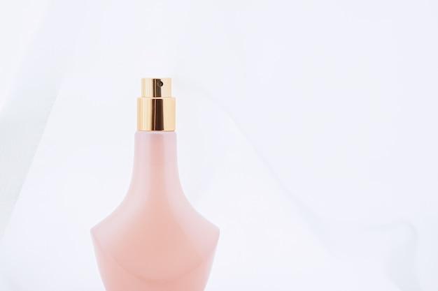 Vintage roze en gouden parfumflesje en schoonheid en cosmetica van witte zijde