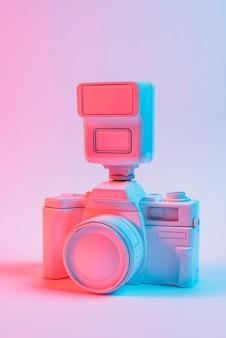 Vintage roze geschilderde camera met lens tegen roze achtergrond