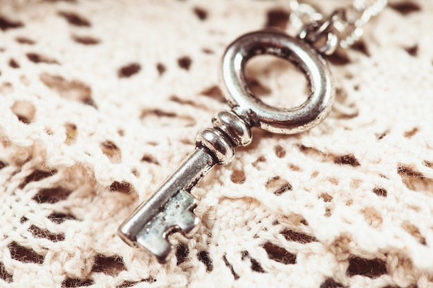 Vintage sleutel op het witte verouderde kant