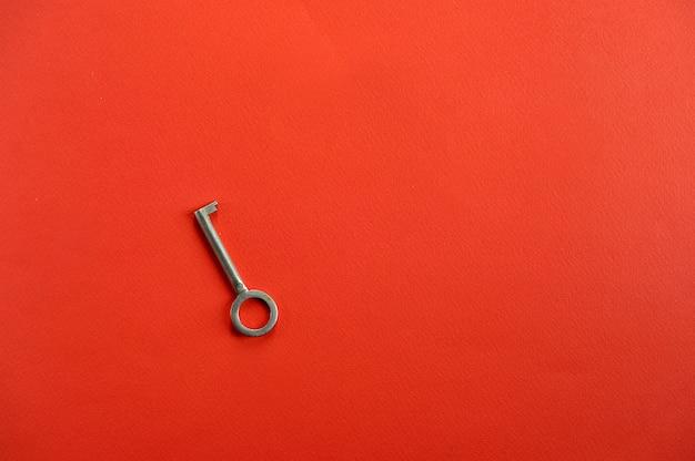 Vintage sleutel op rode achtergrond met ruimte voor tekst