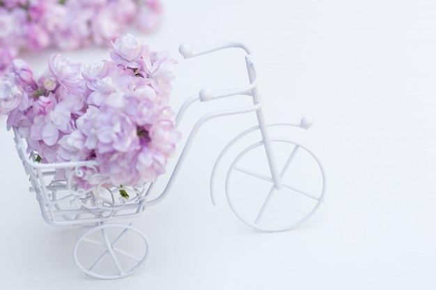 Vintage speelgoedfiets wit. boeket van lila, vakantie decoratie.