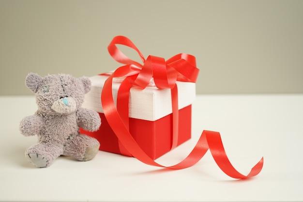 Vintage teddybeer zittend op het nachtkastje naast een geschenkdoos gebonden met helder rood lint