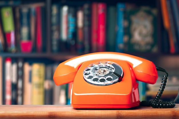 Vintage telefoon in het kantoor op de boekenplank