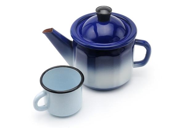 Vintage theepot in blauw met een mok op een afgelegen wit