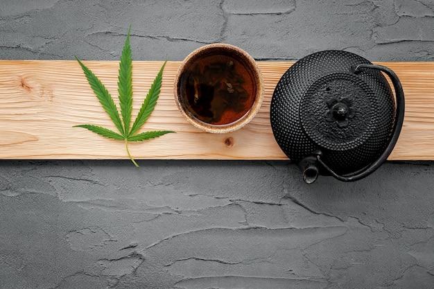 Vintage theepot met cannabis kruidenthee en verse marihuanabladeren opgezet op beton.