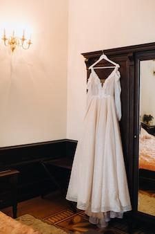 Vintage trouwjurk opknoping op een houten hanger.
