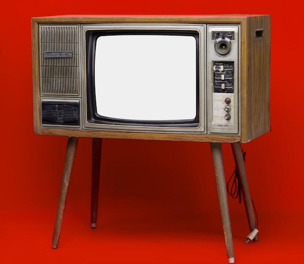 Vintage tv: oude retro tv-toestel geïsoleerd op rode achtergrond.