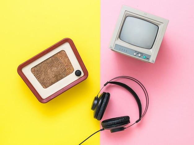 Vintage tv, radio en koptelefoon met draad op een tweekleurige achtergrond. beelden van vintage techniek.