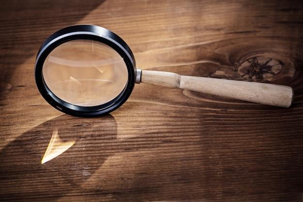 Vintage vergrootglas op oude houten plank