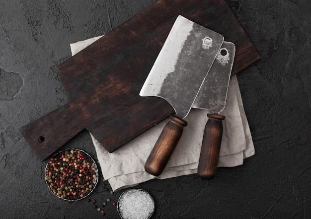 Vintage vleesmes bijl op vintage snijplank en zwarte stenen tafel.