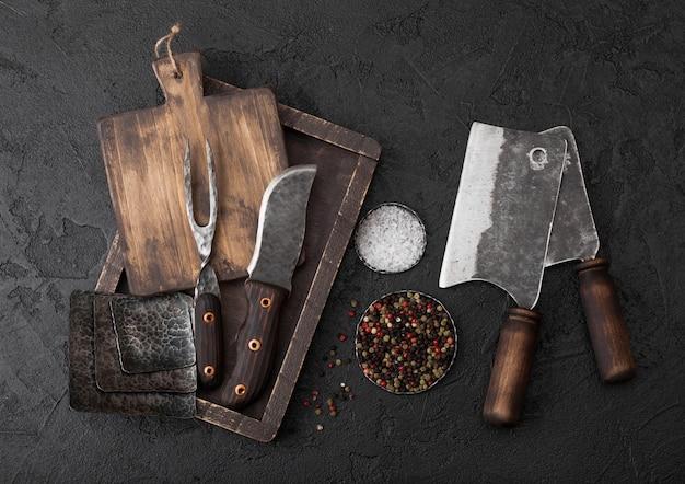 Vintage vleesmes en vork en bijl met vintage snijplank