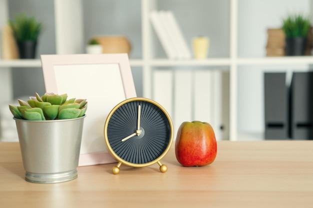 Vintage wekker en appel op houten bureau