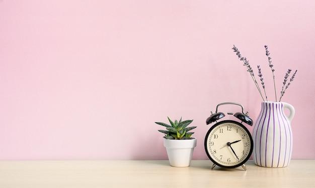 Vintage wekker en huisplant in witte pot op een houten bureau op een roze muurachtergrond.